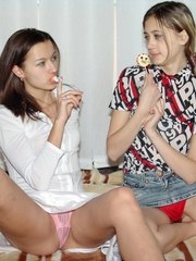 Horny teens both licking lollipops and showing their perfect asses