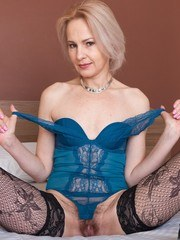 Amanda Blanshe is laying on her bed in her blue lingerie and stockings. She strips