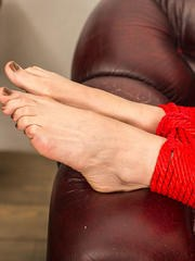 Claudia in her jeans topless and barefoot hogtied within red ropes - photos