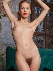Dennie displays her petite naked body and hairy pussy on the sofa.