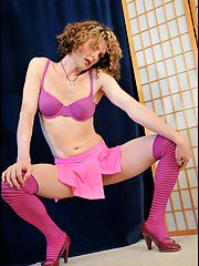 TGirl Delia in hot pink miniskirt ribbon thong and striped thigh highs.