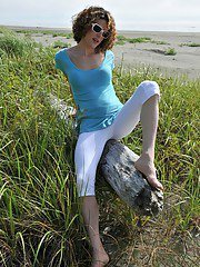 Tranny openly strips out of tight white capri pants at the beach.